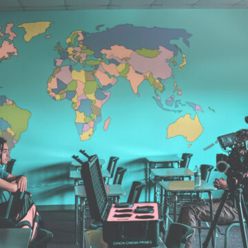 Two people in front of a wrold map. One is filming the other in an interview.