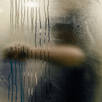 Image by Craig Whitehead - a man wipes condensation from a window