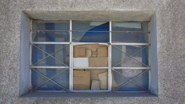 Image by Nicolas Nova - a broken window with cardboard over the missing pane