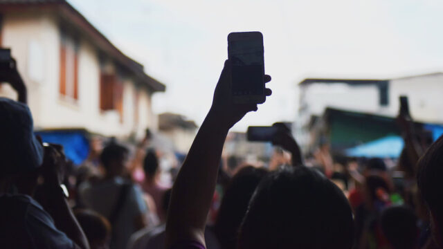 Image by SuHyeon Choi - a hand holds a phone above a crowd