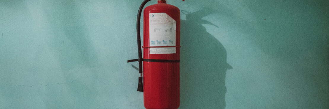 A fire extinguisher hanging on a plain wall