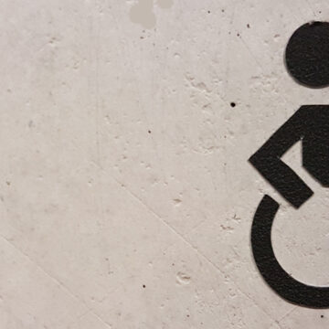 A wheelchair sign stencilled onto a wall